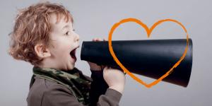 Nuori poika huutamassa megafoniin, päälle piirretty oranssi sydän.